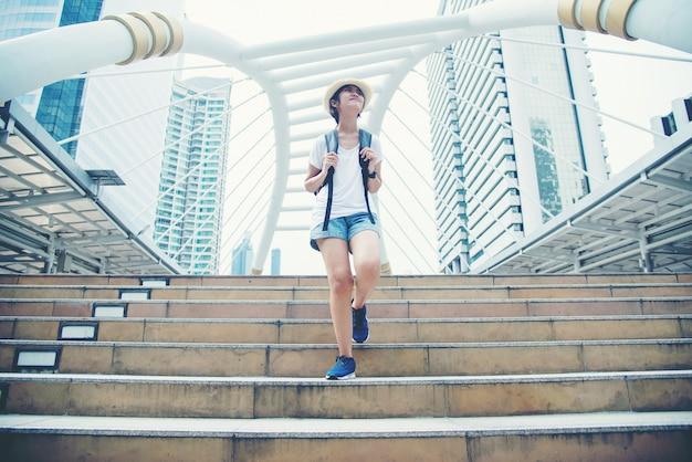 Szczęśliwa uśmiechnięta azjatycka studencka dziewczyna z plecakiem przy miasta tłem