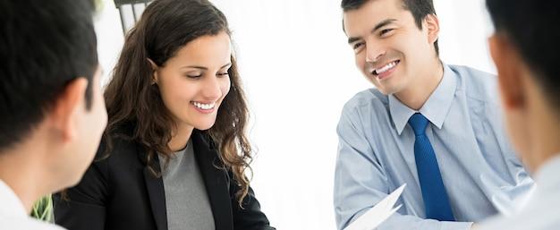 Szczęśliwa uśmiechnięta biznes drużyna dyskutuje dokument przy spotkaniem w biurze