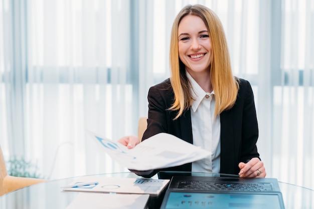 Szczęśliwa uśmiechnięta biznesowa kobieta w biurowym obszarze roboczym