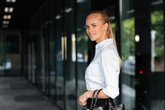 Szczęśliwa uśmiechnięta bizneswoman stojąca i trzymająca torebkę na zewnątrz