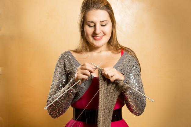 Szczęśliwa uśmiechnięta blond kobieta robi na drutach szalik z igłami