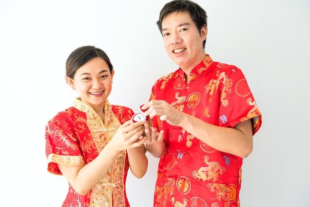 Szczęśliwa uśmiechnięta chińska azjatycka para z czerwonym tradycyjnym strojem cheongsam pokazuje zaręczynowy pierścionek z brylantem na propozycję mariage w 2021 roku na chiński nowy rok.
