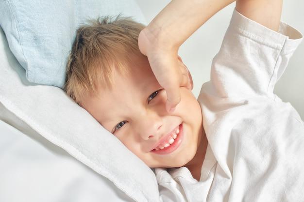 Szczęśliwa uśmiechnięta chłopiec po budzić się rozciągać w łóżku. dzień dobry . portret białego dziecka o szarych oczach i blond włosach, ciesząc się życiem w domu.