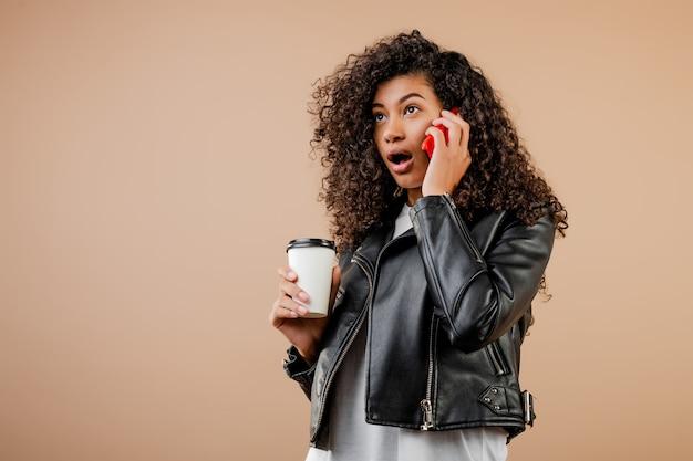 Szczęśliwa uśmiechnięta czarna dziewczyna z telefonem i kawą iść filiżanka odizolowywająca nad brązem