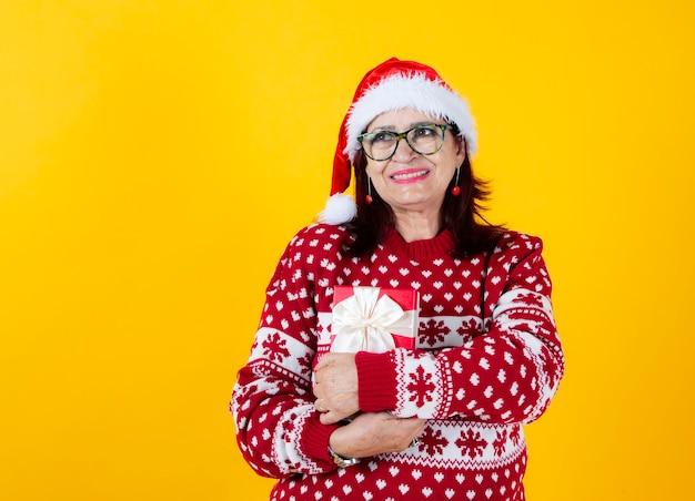 Szczęśliwa uśmiechnięta dojrzała kobieta trzyma pudełko z czerwoną kokardą świąteczny prezent na żółtym tle