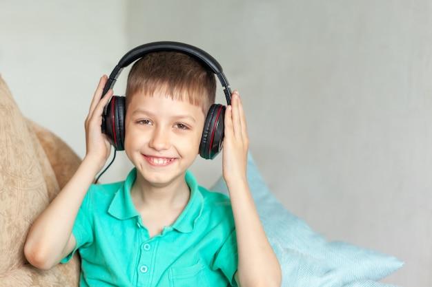 Szczęśliwa uśmiechnięta dzieciak chłopiec w hełmofonach słucha muzyka