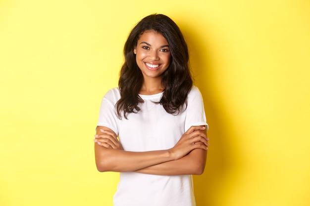 Szczęśliwa uśmiechnięta dziewczyna afroamerykańska w białej koszulce krzyżuje ramiona na piersi i wygląda pewnie