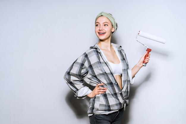 Szczęśliwa uśmiechnięta dziewczyna malarz trzyma wałek do malowania ścian, robi naprawy