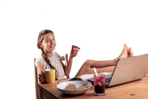 Szczęśliwa uśmiechnięta dziewczyna o wyrazistej twarzy emocjonalnej siedząca przy stole z laptopem, jedząca chleb z dżemem i trzymająca filiżankę herbaty na białym tle