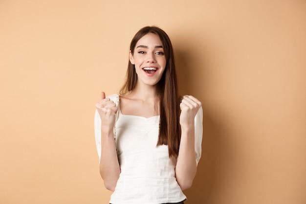 Szczęśliwa uśmiechnięta dziewczyna świętuje zwycięstwo, pompuje pięścią i mówi tak, osiąga cel, triumfuje lub motywuje, stojąc na beżowym tle.