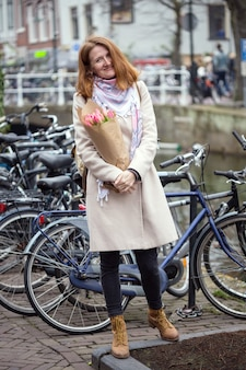 Szczęśliwa uśmiechnięta dziewczyna trzyma bukiet tulipanów stojąc na ulicy amsterdamu