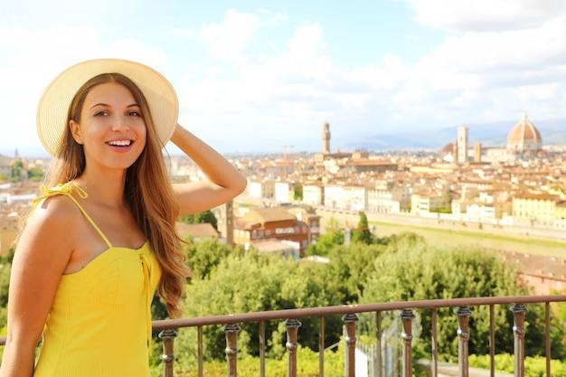 Szczęśliwa uśmiechnięta dziewczyna turystyczny we florencji, włochy. portret młodej kobiety odwiedzających region toskanii we włoszech.
