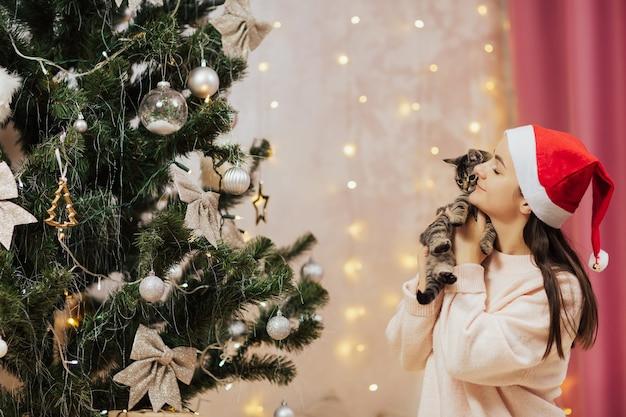 Szczęśliwa uśmiechnięta dziewczyna w czerwonym kapeluszu świętego mikołaja trzyma małego kotka. choinka ozdobiona jest mieniącymi się srebrnymi kulkami i girlandami.