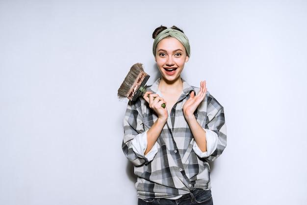 Szczęśliwa uśmiechnięta dziewczyna w kraciastej koszuli koloruje ściany w swoim nowym mieszkaniu, trzyma pędzel