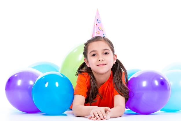 Szczęśliwa uśmiechnięta dziewczyna w pomarańczowej koszulce leżącej na podłodze z kolorowych balonów - na białym tle