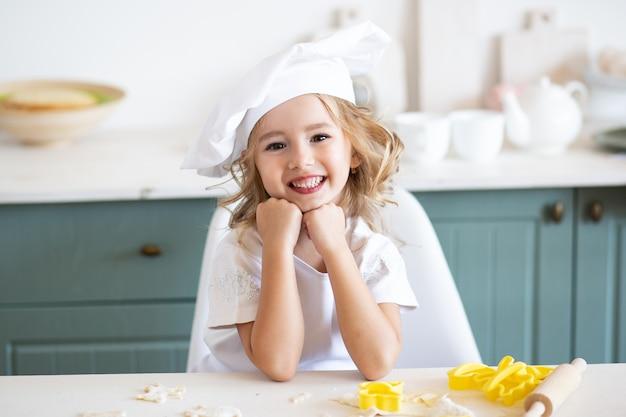 Szczęśliwa uśmiechnięta dziewczyna w szefa kuchni toque w kuchni