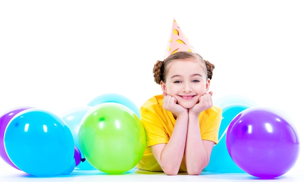 Szczęśliwa uśmiechnięta dziewczyna w żółtej koszulce leżącej na podłodze z kolorowych balonów - na białym tle