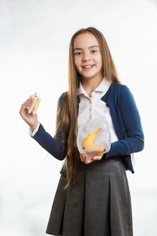Szczęśliwa uśmiechnięta dziewczyna wyjmując kanapkę z pudełka na lunch na białym tle