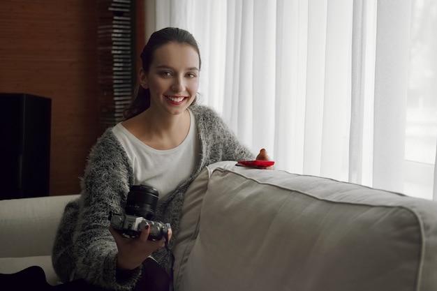 Szczęśliwa uśmiechnięta dziewczyna z aparatem fotograficznym i telefonem w ona ręki