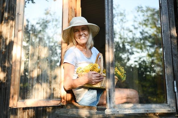 Szczęśliwa uśmiechnięta emocjonalna starsza kobieta pozuje przez otwarte okno w starym drewnianym wiejskim domu w słomkowym kapeluszu z koszem kwiatów