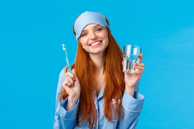 Szczęśliwa uśmiechnięta i beztroska rudowłosa entuzjastyczna dziewczyna w masce snu, piżamie, trzymająca szklaną wodę i szczoteczkę do zębów, dbająca o higienę jamy ustnej, codzienna rutyna, niebieska ściana
