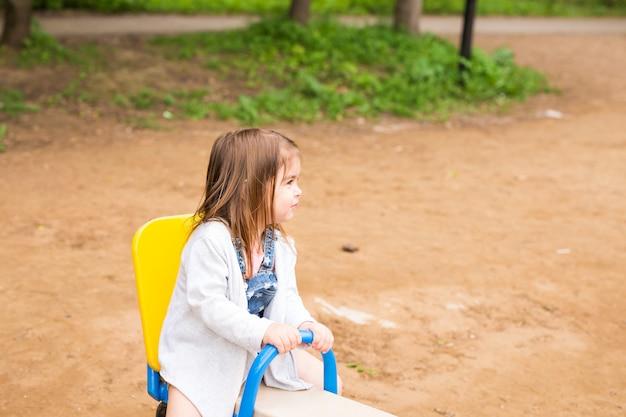 Szczęśliwa uśmiechnięta i piękna dziewczyna dzieciak zabawy w parku w jasny, słoneczny dzień