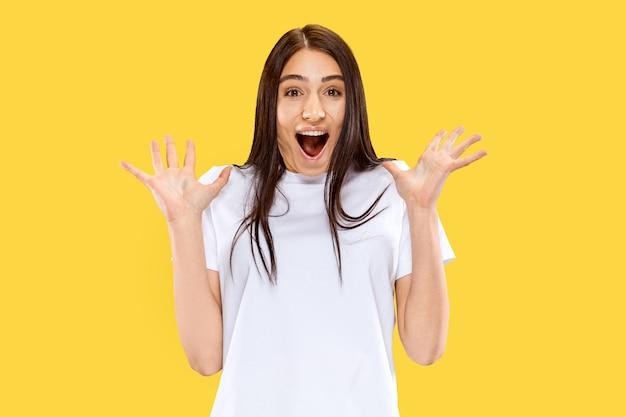 Szczęśliwa uśmiechnięta i zdziwiona dziewczyna. piękny portret kobiety w połowie długości na białym tle na żółtej ścianie. młoda uśmiechnięta kobieta. negatywna przestrzeń. wyraz twarzy, koncepcja ludzkich emocji.