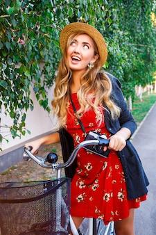 Szczęśliwa uśmiechnięta kobieta bawiąca się i zaskakująca figlarnymi emocjami, spacerująca samotnie na stylowym rowerze retro w parku miejskim, ubrana w ciepły sweter w czerwonej sukience i vintage słomkowy kapelusz, ma kręcone długie blond włosy.