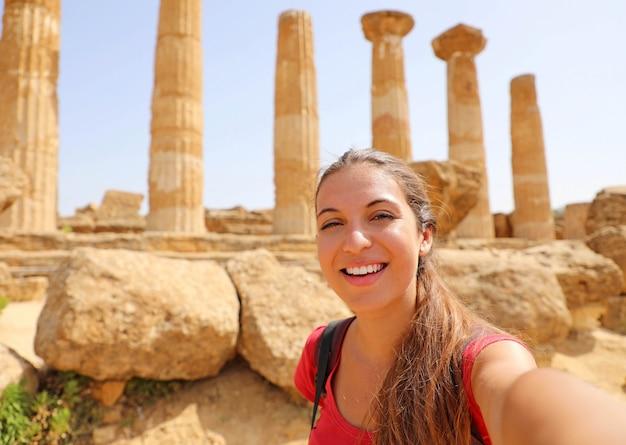 Szczęśliwa uśmiechnięta kobieta biorąc autoportret z grecką świątynią na tle w dolinie świątyń w agrigento, włochy