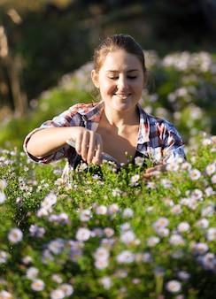 Szczęśliwa uśmiechnięta kobieta cięcia kwiatów w ogrodzie w słoneczny dzień