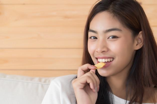 Szczęśliwa, uśmiechnięta kobieta jedząca chipsy lub chrupiący smażony ziemniak