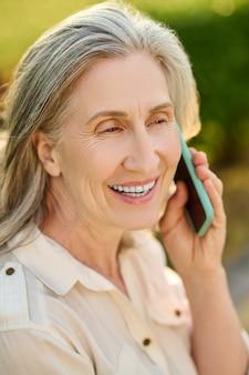 Szczęśliwa uśmiechnięta kobieta komunikująca się za pomocą smartfona