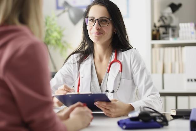 Szczęśliwa uśmiechnięta kobieta lekarz przyjmuje pacjenta w klinice udanej koncepcji ivf