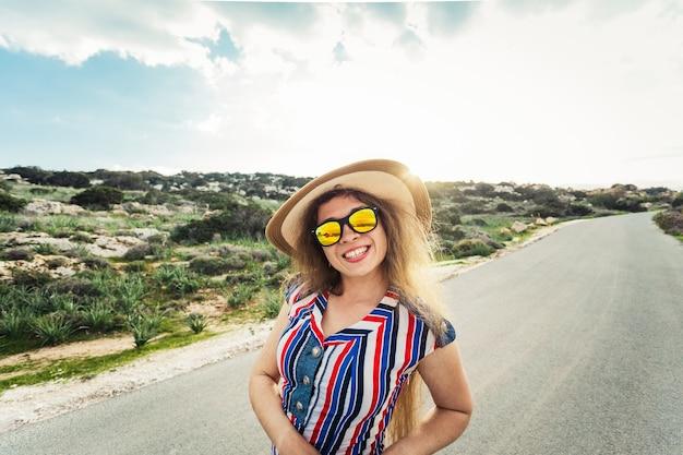 Szczęśliwa uśmiechnięta kobieta na wakacjach z kapeluszem słonecznym i okularami.