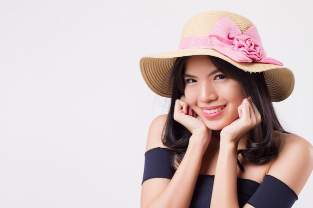 Szczęśliwa uśmiechnięta kobieta nosi kapelusz podróży lato. portret podróżnika pozytywne optymistyczne kobiety, studio białe na białym tle z koncepcją wakacje lub wakacje. młoda dorosła piękna dziewczyna azjatycka modelka