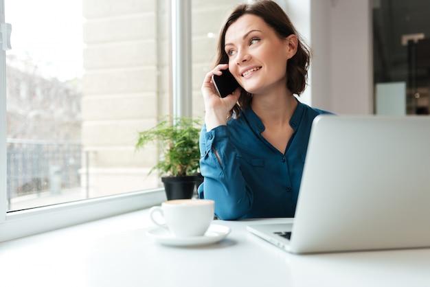 Szczęśliwa uśmiechnięta kobieta opowiada na telefonie komórkowym