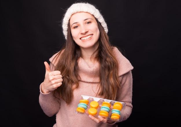 Szczęśliwa uśmiechnięta kobieta pokazuje kciuk do góry trzymając pudełko z makaronikami.