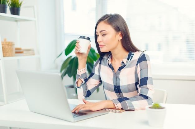 Szczęśliwa uśmiechnięta kobieta pracuje z laptopem i pije kawę