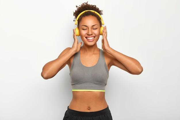 Szczęśliwa uśmiechnięta kobieta relaksuje się po ćwiczeniach, nosi sportowy strój, słucha muzyki przez nowoczesne słuchawki, ma dobry nastrój