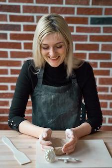 Szczęśliwa uśmiechnięta kobieta robi ceramicznemu garncarstwu. koncepcja dla niezależnej kobiety