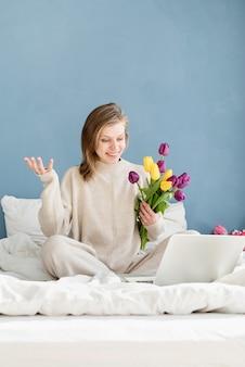 Szczęśliwa uśmiechnięta kobieta siedzi na łóżku w piżamie, z przyjemnością ciesząc się kwiatami, rozmawiając za pomocą laptopa