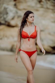 Szczęśliwa uśmiechnięta kobieta spaceru w czerwonym bikini na plaży.