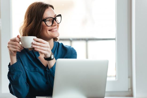 Szczęśliwa uśmiechnięta kobieta trzyma filiżankę kawy
