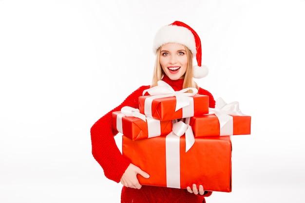 Szczęśliwa uśmiechnięta kobieta trzyma pudełka z teraźniejszością na boże narodzenie