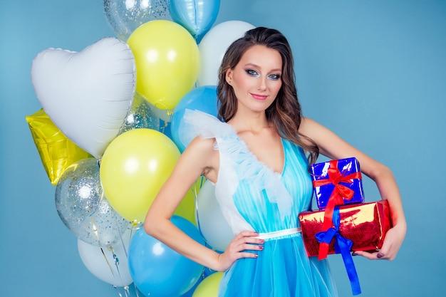 Szczęśliwa uśmiechnięta kobieta trzyma pudełko na niebieskim tle i helowe żółte, niebiesko-białe balony.pudełka prezentów w rękach zaskoczonej dziewczyny w pięknej sukni wieczorowej