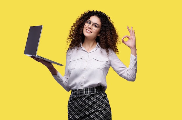 Szczęśliwa uśmiechnięta kobieta ubrana w białą koszulę trzyma laptopa i pokazuje ok gest na żółtej odizolowanej ścianie. koncepcje zakupów online, bankowość internetowa