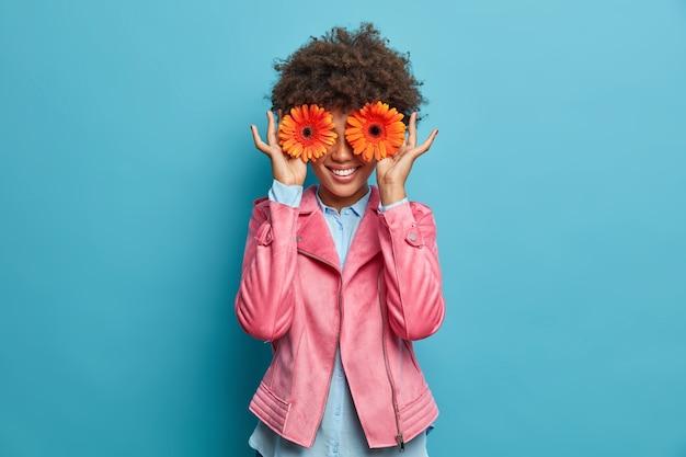 Szczęśliwa uśmiechnięta kobieta ukrywa twarz z dwoma pomarańczowymi gerbery, lubi kwiaty, wyraża szczęście i radość. wesoła kwiaciarnia zamierza zrobić piękny bukiet na sprzedaż, pracuje w kwiaciarni