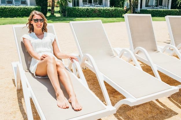 Szczęśliwa uśmiechnięta kobieta w białej sukni siedzi na krześle