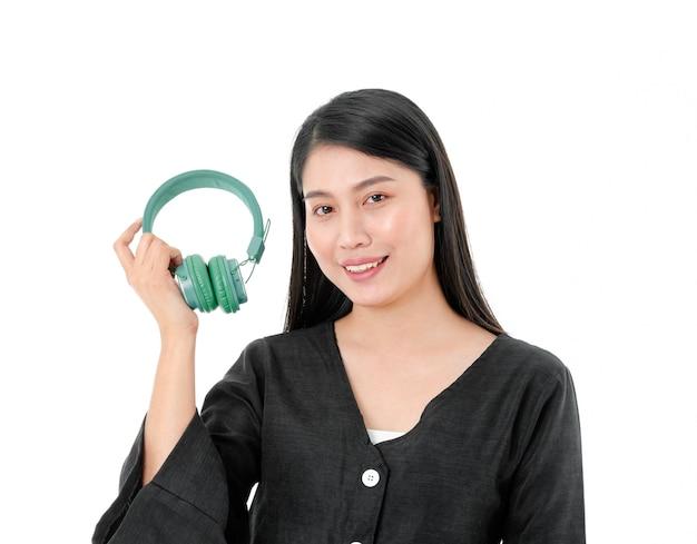 Szczęśliwa uśmiechnięta kobieta w czarnej sukni trzymająca w dłoni zielone słuchawki na białym tle