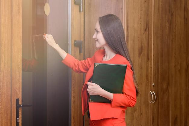 Szczęśliwa uśmiechnięta kobieta w czerwonym kostiumu z dokumentami w ręce puka do drzwi do szefa